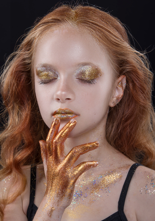 Cute redhead teenage model with bright makeup and colorful glitter and sparkles on her face and body