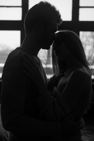Silhouette of the loving couple in the bedroom having a good time