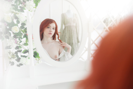 Tender portrait of a young dreamy redhead woman wearing beautiful vintage dress. She is sitting in front of the mirror with naked breast