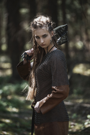 Viking woman with hammer wearing traditional warrior clothes in a deep mysterious forest Foto de archivo