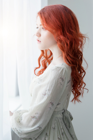 Tender retro portrait of a young beautiful dreamy redhead woman Imagens