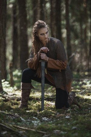 Viking woman with sword wearing traditional warrior clothes in a deep mysterious forest