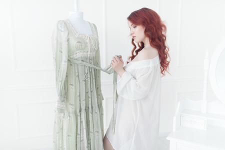 Tender portrait of a young dreamy redhead woman in nightdress. She is standing in dress room and planning to wear beautiful vintage dress Imagens