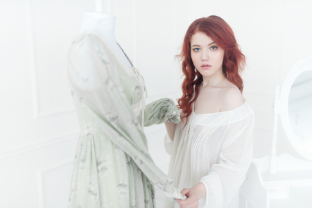 Tender portrait of a young dreamy redhead woman in nightdress. She is standing in dress room and planning to wear beautiful vintage dress Banco de Imagens - 102395333