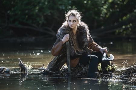Wikingerfrau mit Schwert und Hammer, die traditionelle Kriegerkleidung in einem tiefen geheimnisvollen Wald tragen Standard-Bild