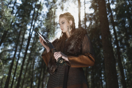 Viking woman with hammer wearing traditional warrior clothes in a deep mysterious forest Stock Photo