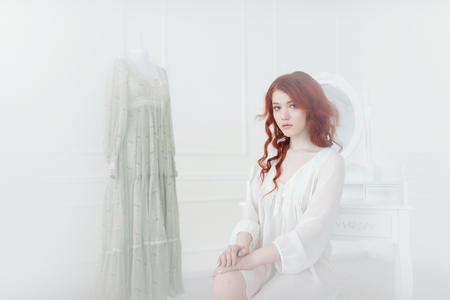 Tender portrait of a young dreamy redhead woman in nightdress. She is sitting in dress room and planning to wear beautiful vintage dress