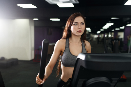 Attractive fitness girl doing exercise on machine treadmill. Pretty girl doing workout at modern fitness gym Stock Photo
