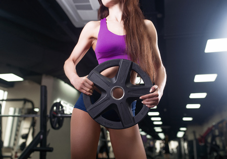 Athlete woman working out with barbell. Bikini fitness girl in sportswear doing exercise in gym
