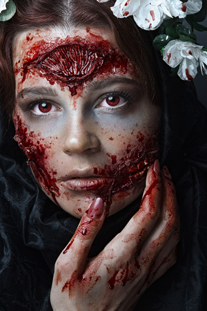 Portrait of bloody horrible scary zombie girl in a halloween festive makeup. Red eyes 写真素材