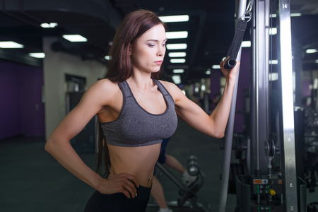 Athlete girl in sportswear working out and training her arms and shoulders with exercise machine in gym