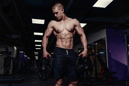Handsome strong athletic man pumping up muscles with dumbbells. Muscular bodybuilder with naked sport torso doing exercises in gym
