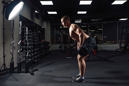 Athletic young man doing exercises with barbell in gym. Handsome muscular bodybuilder guy is working out. Backstage