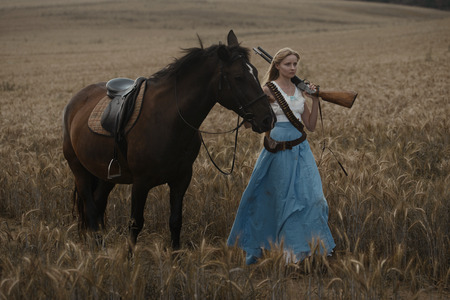 Portrait of a beautiful female cowgirl with shotgun from wild west riding a horse in the outback Archivio Fotografico