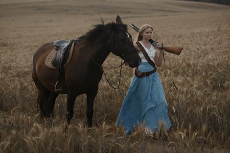 Retrato de una hermosa mujer vaquera con escopeta del salvaje oeste a caballo en el interior Foto de archivo