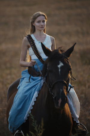 Portrait of a beautiful female cowgirl with shotgun from wild west riding a horse in the outback 写真素材