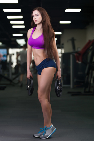 Athletic young woman showing muscles after workout in gym 写真素材