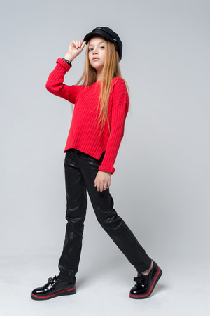 Portrait of beautiful young redhead girl wearing red sweater and black pants posing in studio