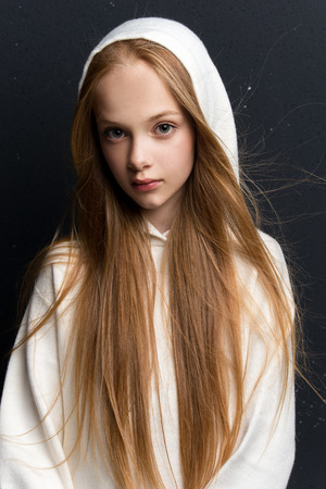 Portrait of beautiful young redhead girl posing in studio