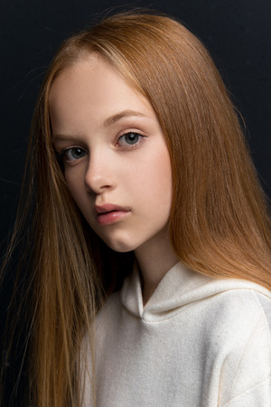 Close-up portrait of beautiful young redhead in studio on black background 写真素材