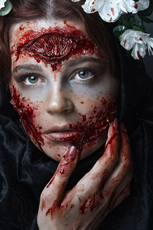 Portrait of bloody horrible scary zombie girl in a halloween festive makeup