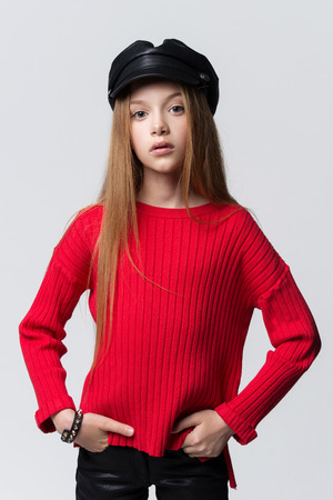 Close-up portrait of beautiful young redhead girl wearing red sweater posing in studio