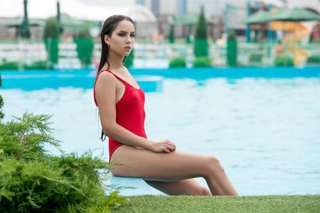 Beautiful sexy woman with healthy tanned skin in bikini relaxing in swimming pool water