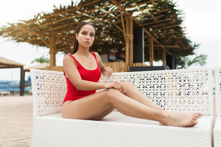 Young woman in swimsuit relaxing on sun lounger near the pool 写真素材