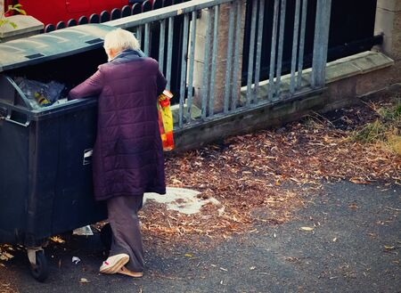 homeless man searching the trash