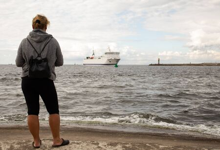 tourist on the sea shore looking at the ship, merchant ship entering the Baltic port in Poland