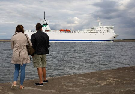 merchant ship entering the Baltic port in Poland, tourists looking at the ship entering the port