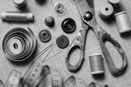 Matériel de couture. Composition de fournitures de couture sur fond de toile. Version horizontale noir et blanc. Banque d'images