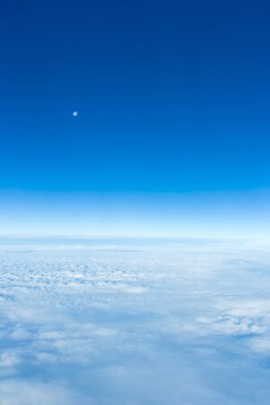 cloud and sky with moon as seen through window of airplane Archivio Fotografico