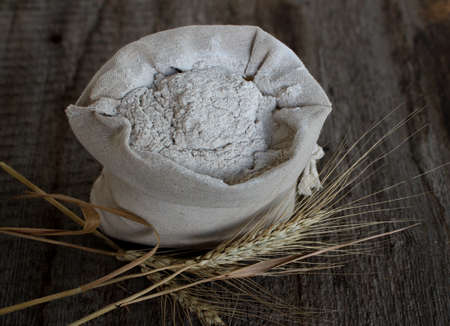 Wheat weazing and a linen bag with flour on a wooden background. Reklamní fotografie