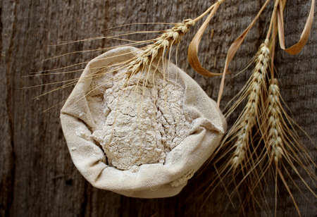 Golden rye ears and a linen bag with rye flour on a wooden background.