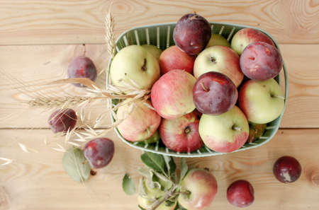 Autumn still life with apples, plums, autumn leaves. Ripe fruit crop in a basket on a wooden surface. 免版税图像