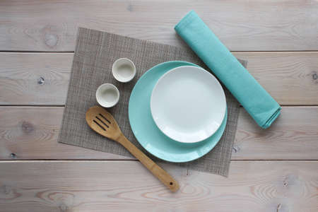 White and turquoise plate, wooden kitchen spoon, turquoise napkin on a gray-brown backing. Dishes on a wooden background. The view from the top. For mockup. Reklamní fotografie - 156473384