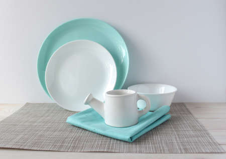 White and turquoise dishes on a woven napkin on a wooden table. Two plates, a bowl, a milk jug in the shape of a watering can. Kitchen utensils for mockup. 免版税图像