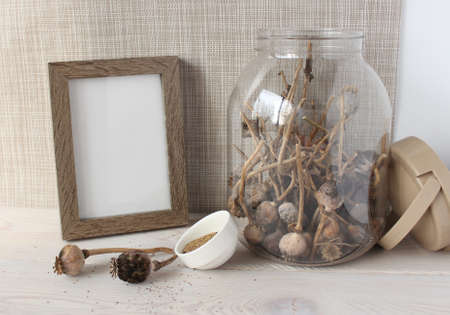 Glass jar with dry poppy heads, poppy seeds in a white Cup, wooden photo frame. Objects on a wooden background. For mockup. 免版税图像 - 156474064