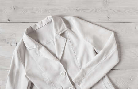 White women's short linen jacket with buttons and long sleeves. Women's elegant clothing on a light wooden background. For mockup. 免版税图像 - 156445650