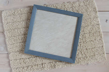 Blue photo frame on a fluffy white rug. Objects on a light wooden surface. The view from the top. For mockup.