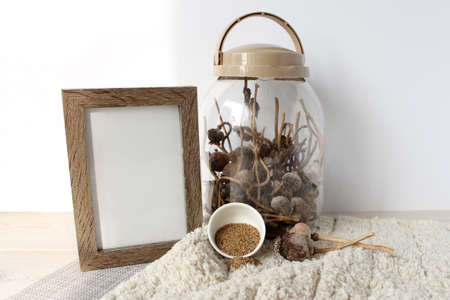 Glass jar with dry poppy heads, poppy seeds in a white Cup, wooden photo frame. Objects on a fluffy white rug. For mockup. 免版税图像