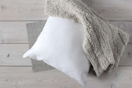 White pillow and soft fluffy rug on the wooden surface. The view from the top. For mockup.