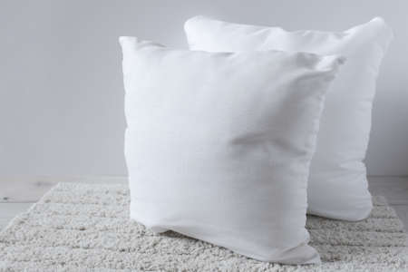 Two white pillows on a fluffy rug. Objects on a wooden surface. For mockup.
