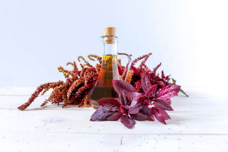 A branch of red amaranth with leaves and seeds, oil in a vessel. Medicinal plant. Useful for health, edible herb.