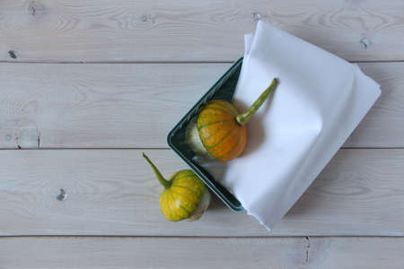 Turquoise basket with white fabric and decorative pumpkins. Objects on a light wooden surface. 免版税图像 - 157065936