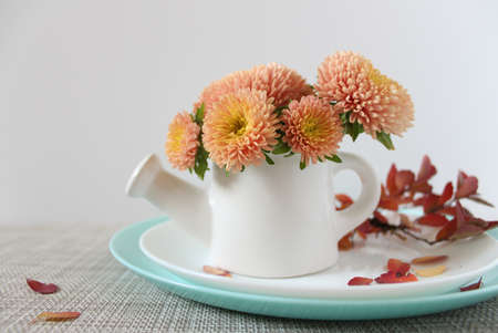 A bouquet of chrysanthemums in a white decorative teapot. A twig with red autumn leaves on a white plate. 免版税图像 - 157065820