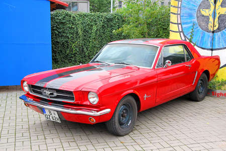 BERLIN, GERMANY - SEPTEMBER 12, 2013  Red Ford Mustang retro muscle car at the city street