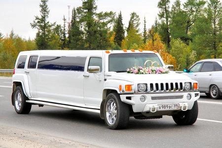 garish: NOVYY URENGOY, RUSSIA - AUGUST 31, 2012  White Hummer H3 wedding limousine at the city street