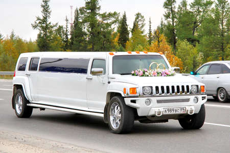 NOVYY URENGOY, RUSSIA - AUGUST 31, 2012  White Hummer H3 wedding limousine at the city street